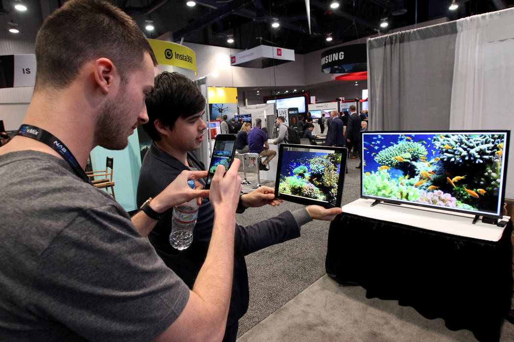 Robin Sho Moser, CEO and co-founder of eyecandylab, right, shows augmented reality to Dalla Costa of Italy during the National Association of Broadcasters Show at the Las Vegas Convention Center W ...