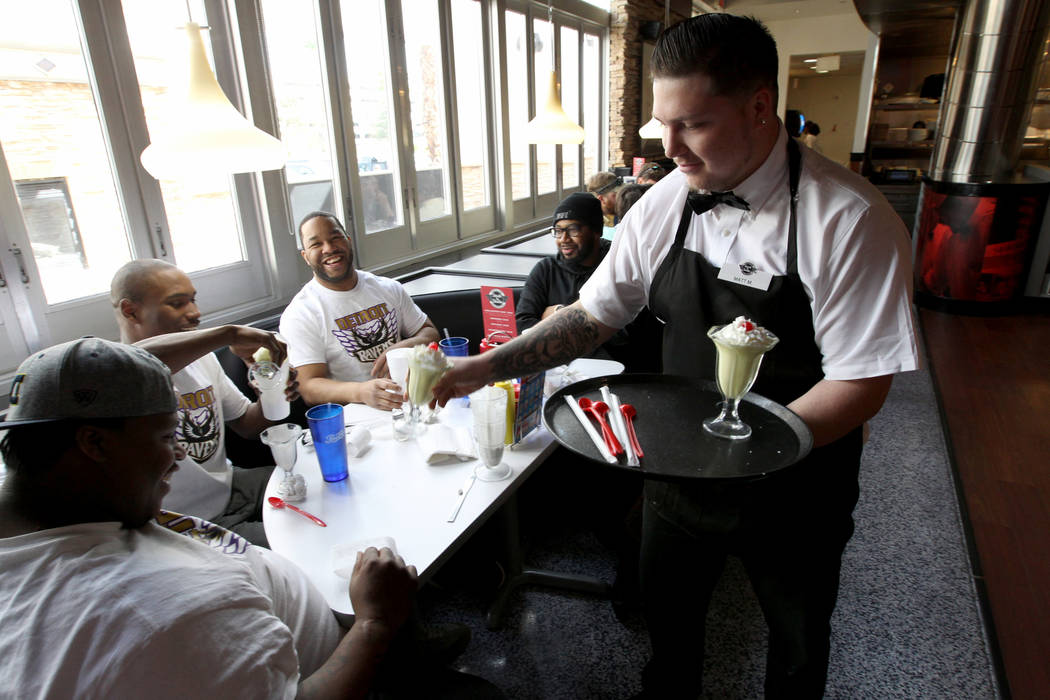 Matt Murrah gives free sample milkshakes to, from left, Mario Carson, Jose Morris, El-Tee Sims and Keith Woods of Detroit at Steak 'n Shake inside Hooters Hotel on opening day Thursday, April 5, 2 ...