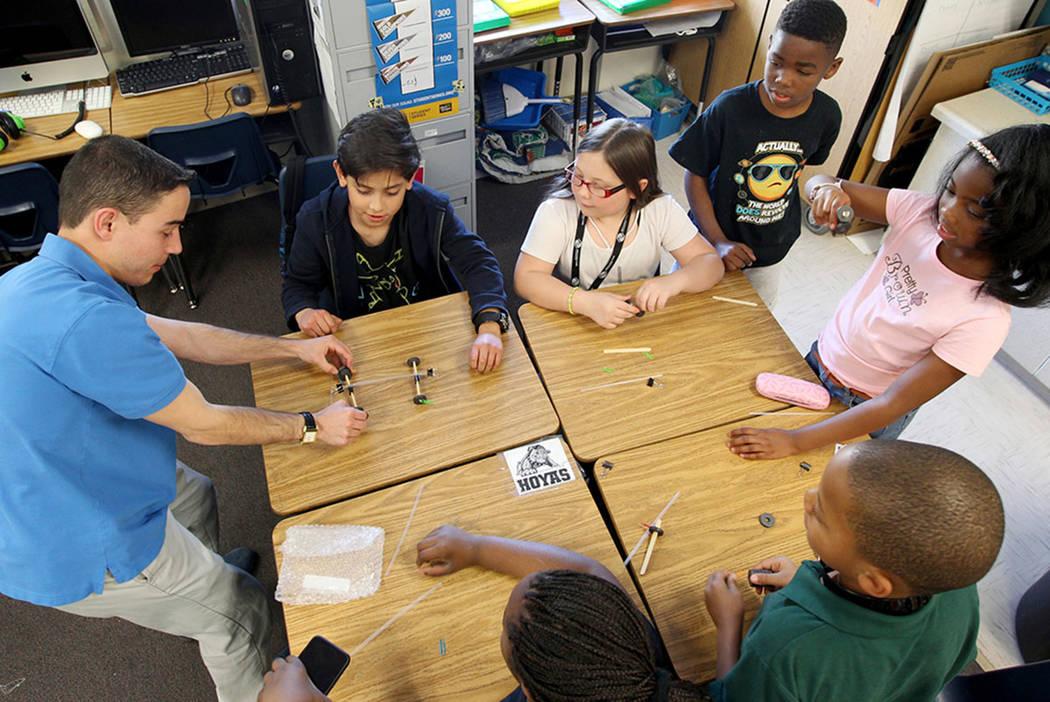 Booker Elementary School teacher Derek Faraldo, left, shows how magnets can power a car, Wednesday, April 4, 2018. With Faraldo are, clockwise from top, Ricardo Lopez, Cassie Long, Aukai Thomas, T ...