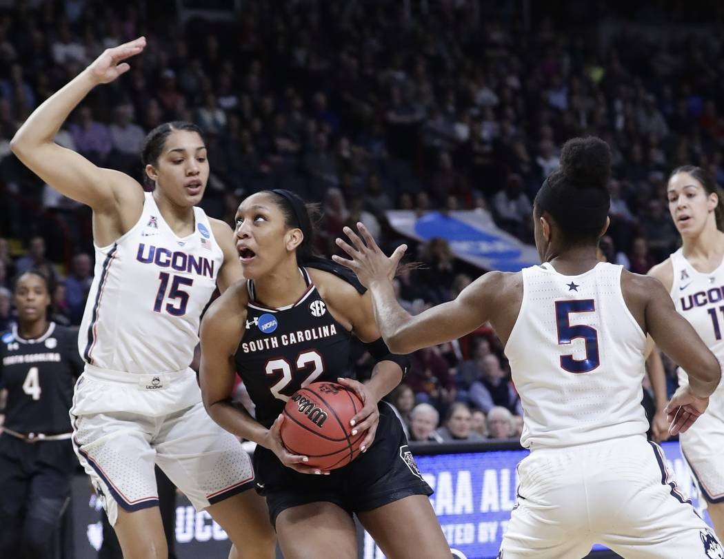 South Carolina's A'ja Wilson (22) drives past Connecticut's Gabby Williams (15) and Crystal Dangerfield (5) during the first half of a regional final at the a women's NCAA college basketball tourn ...