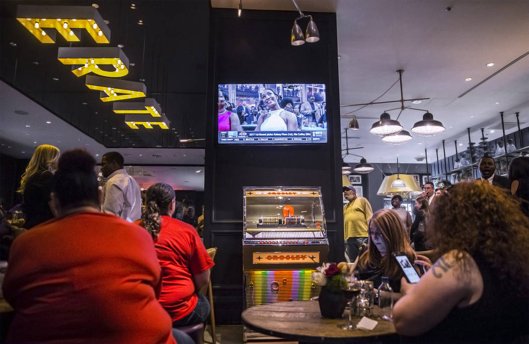Fans watch the first round of the 2018 WNBA draft during a party hosted by the Las Vegas Aces at Libertine Social on Thursday, April 12, 2018, at the Mandalay Bay hotel-casino, in Las Vegas. Benja ...