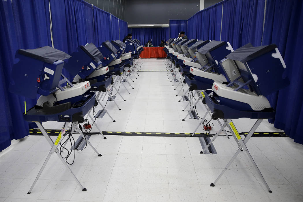 In this Tuesday, March 13, 2018 photo, voters cast their ballots in Illinois primary elections at the city's new early voting super site in downtown Chicago. In Illinois, attempts by hackers in th ...