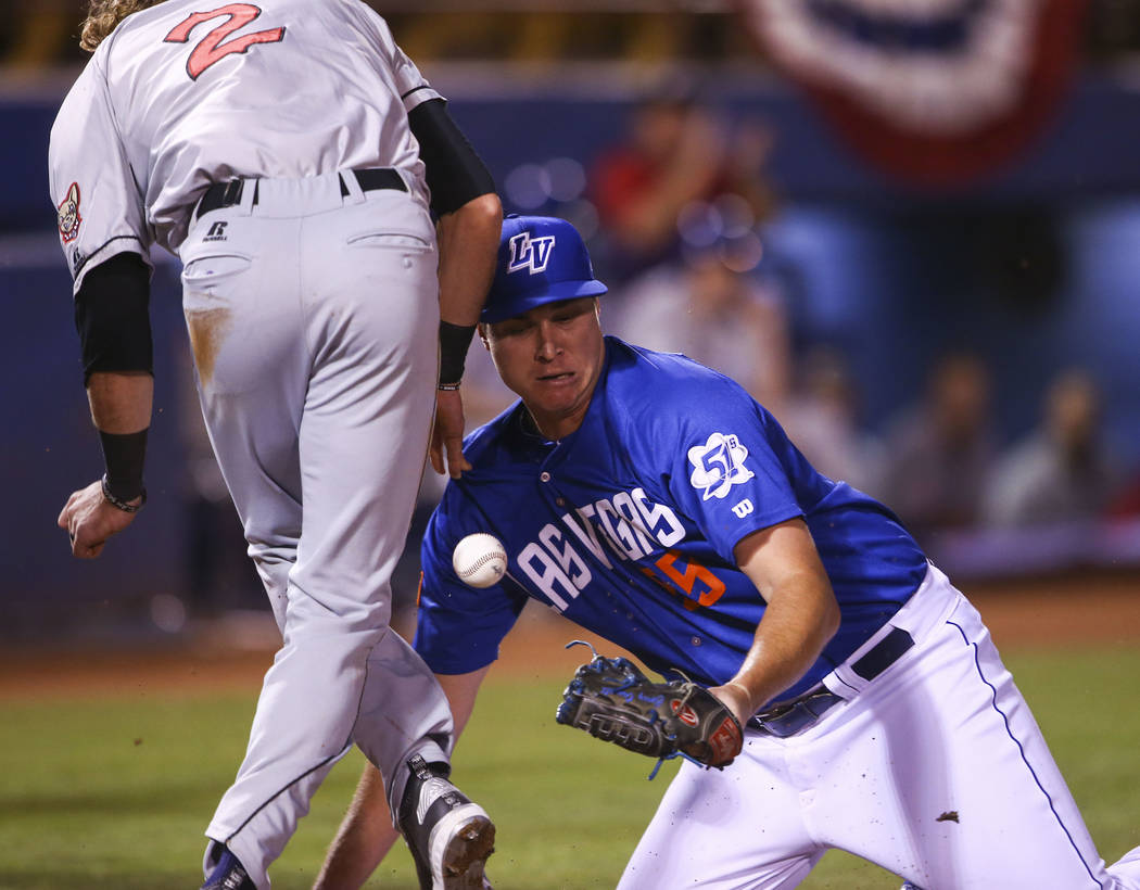 El Paso Chihuahuas center fielder Travis Jankowski (2) scores a run as Las Vegas 51s pitcher Corey Oswalt (55) comes up short on the tag during the opening day baseball game at Cashman Field in La ...