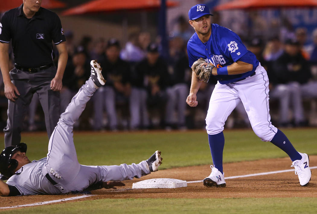 Las Vegas 51s third baseman David Thompson (8) looks to throw after tagging out El Paso Chihuahuas shortstop Luis Urias (3) during the opening day baseball game at Cashman Field in Las Vegas on Th ...