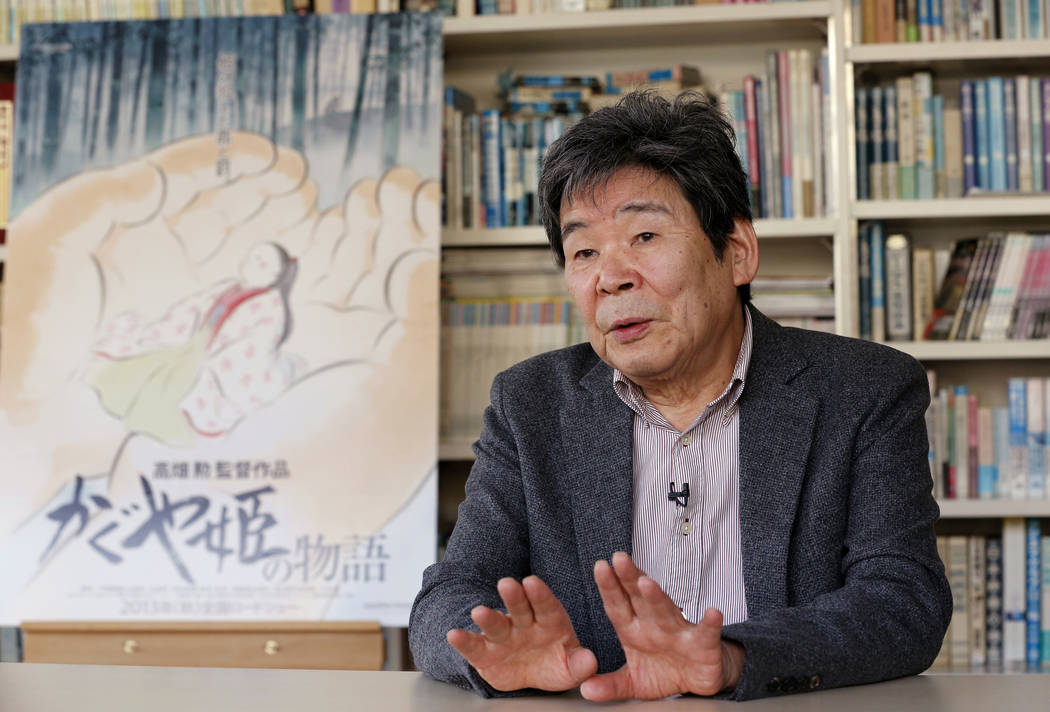 "Japanese animated film director Isao Takahata speaks about his latest film ""The Tale of The Princess Kaguya"" with its poster during an interview at his office, Studio Ghibli, in suburban Tokyo in  ..."
