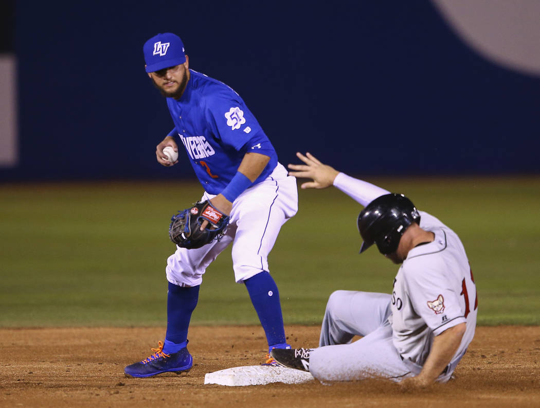 Las Vegas 51s second baseman Gavin Cecchini (2) tags out El Paso Chihuahuas center fielder Nick Schulz (12) during the opening day baseball game at Cashman Field in Las Vegas on Thursday, April 5, ...