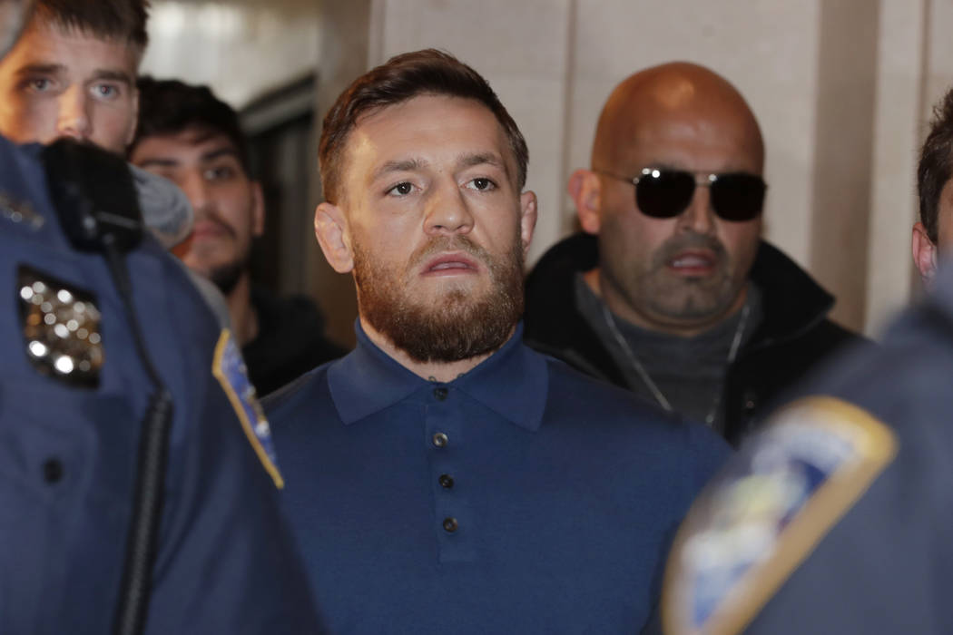 Ultimate fighting star Conor McGregor, center, is escorted by New York Court Police officers after a hearing at the Brooklyn Criminal Court, Friday, April 6, 2018 in New York. McGregor is facing c ...