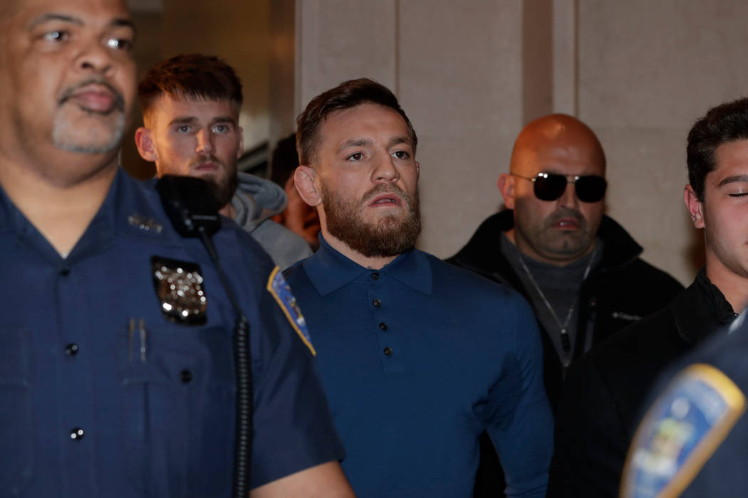Ultimate fighting star Conor McGregor, center, is escorted by New York Court Police officers after a hearing at the Brooklyn Criminal Court, Friday, April 6, 2018, in the Brooklyn borough of New Y ...