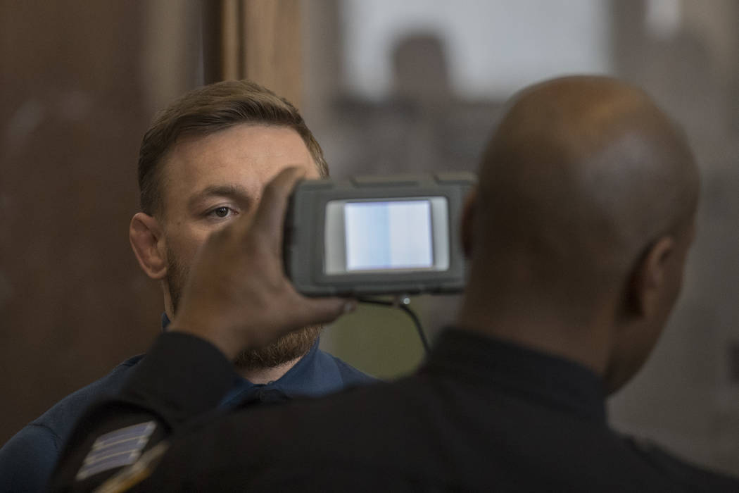 CORRECTS TO BROOKLYN CRIMINAL COURT, NOT BROOKLYN FEDERAL COURT-A court officer conducts an eye scan on Ultimate fighting star Conor McGregor during his arraignment in Brooklyn Criminal Court, Fri ...