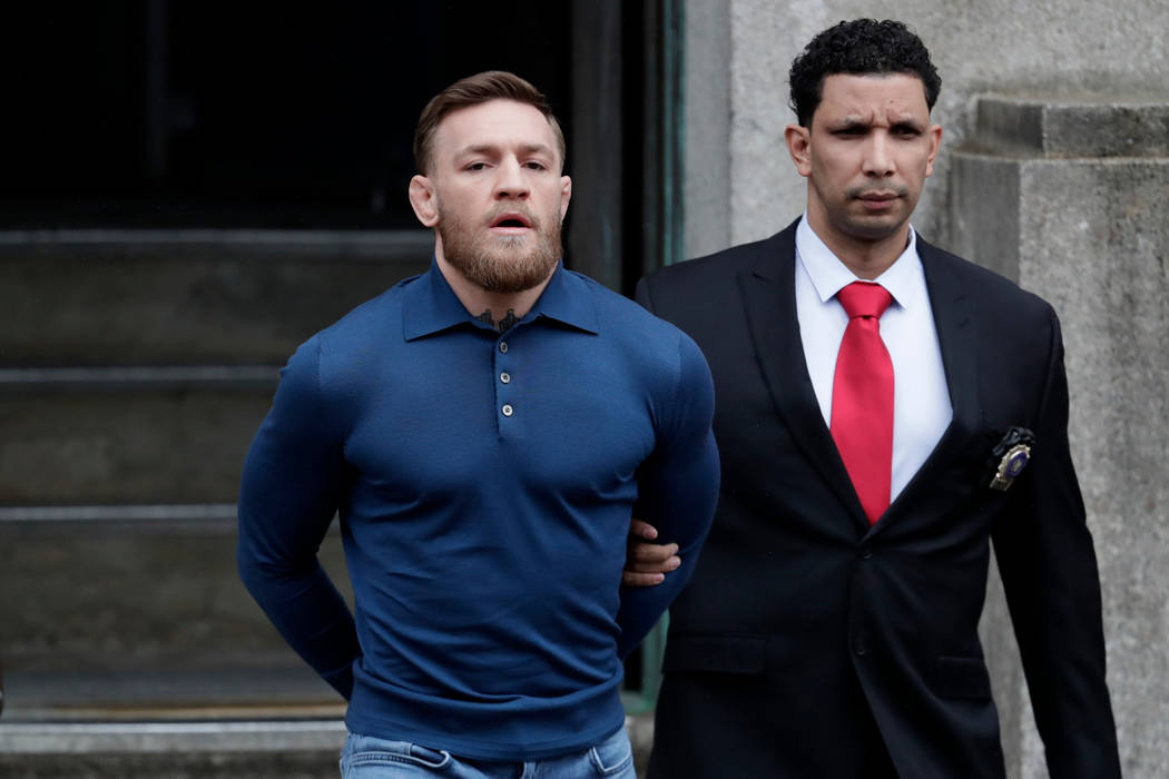 Ultimate fighting star Conor McGregor, left, is led by an official onto an unmarked vehicle while leaving the 78th Precinct of the New York Police Department, Friday, April 6, 2018, in the Brookly ...