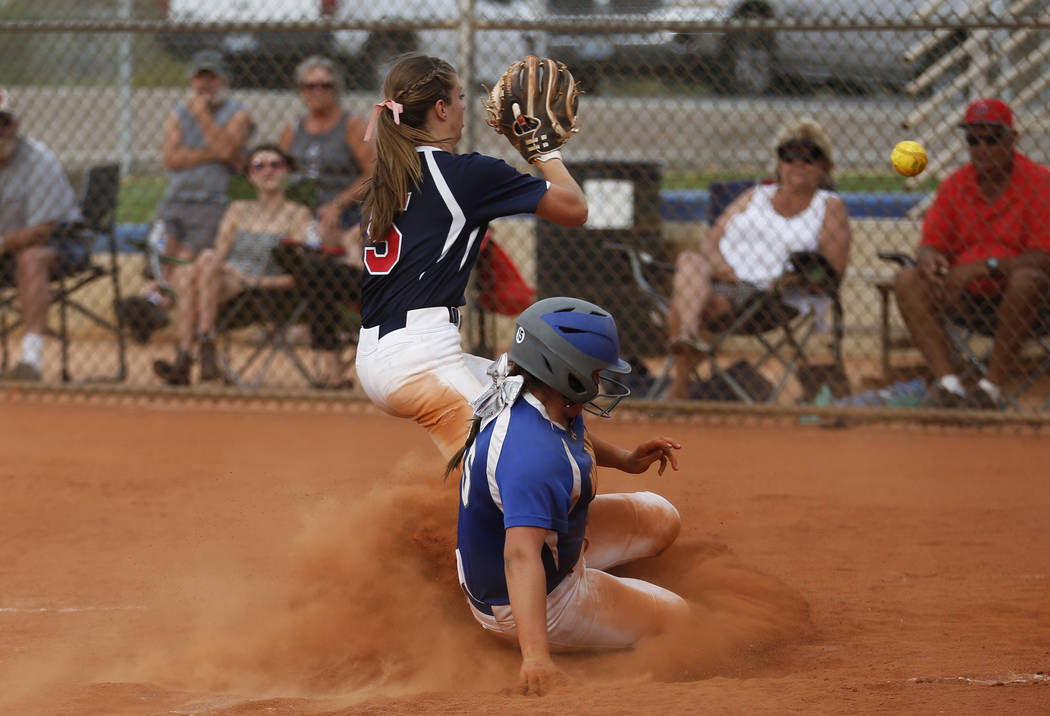Basic's shortstop Mikayla Berg (15) slides safely into home plate as Coronado's pitcher Tatum Spangler (5) receives a throw at Basic High School in Henderson on Friday, April 6, 2018.Basic w ...