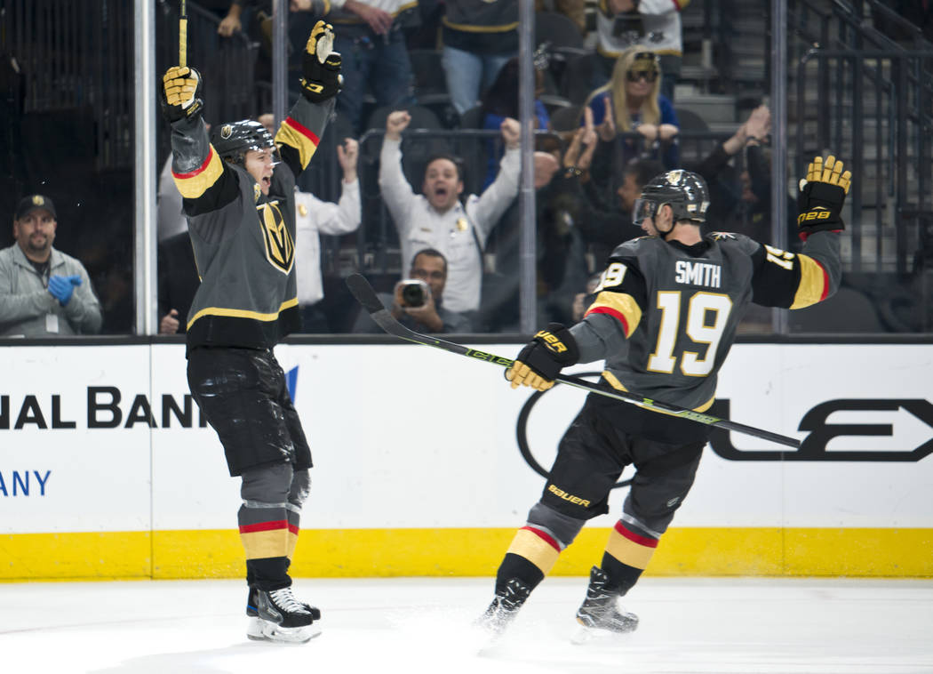 Vegas Golden Knights center William Karlsson (71) celebrates with teammate right ring Reilly Smith (19) after performing the first hat trick in franchise history during their home game against the ...