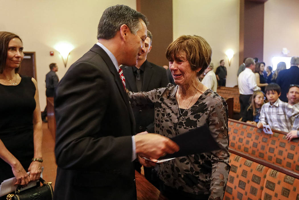 Governor Brian Sandoval, second left, greets Becky Oram, widow of Kent Oram, following a celebration of life ceremony for Oram at Palm Mortuary in Las Vegas on Saturday, April 7, 2018. Oram died l ...