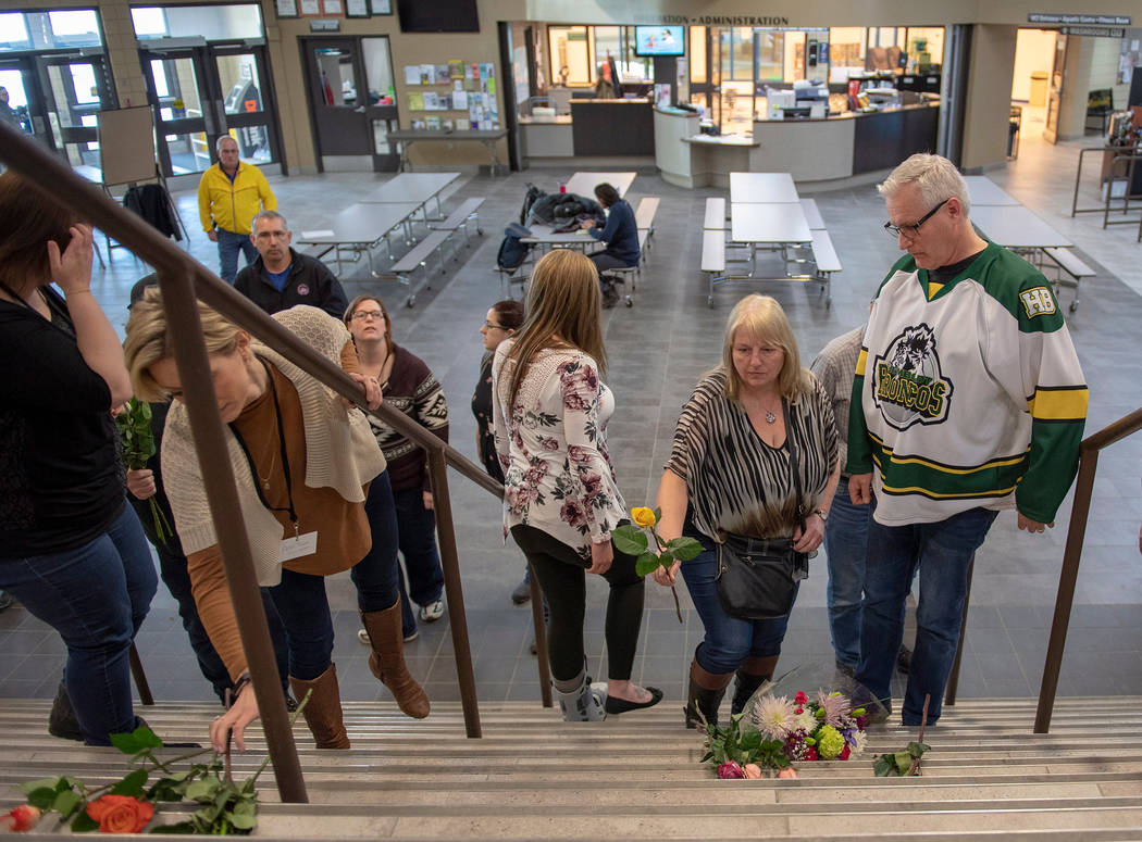 Humboldt mayor Rob Muench, in the Broncos team jersey, along with other mourners lay down flower on the stairs that enter to Elgar Petersen Arena, home of the Humboldt Broncos, in Humboldt, Saskat ...