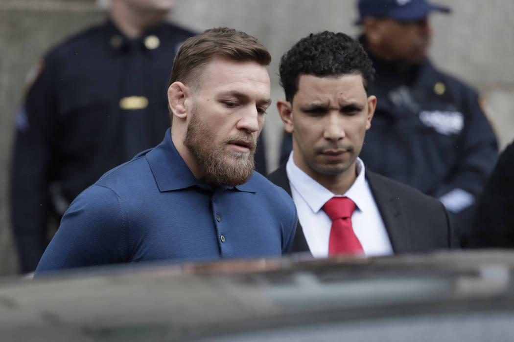 UFC star Conor McGregor, left, is led by an official to an unmarked vehicle while leaving the 78th Precinct of the New York Police Department, Friday, April 6, 2018, in the Brooklyn borough of New ...
