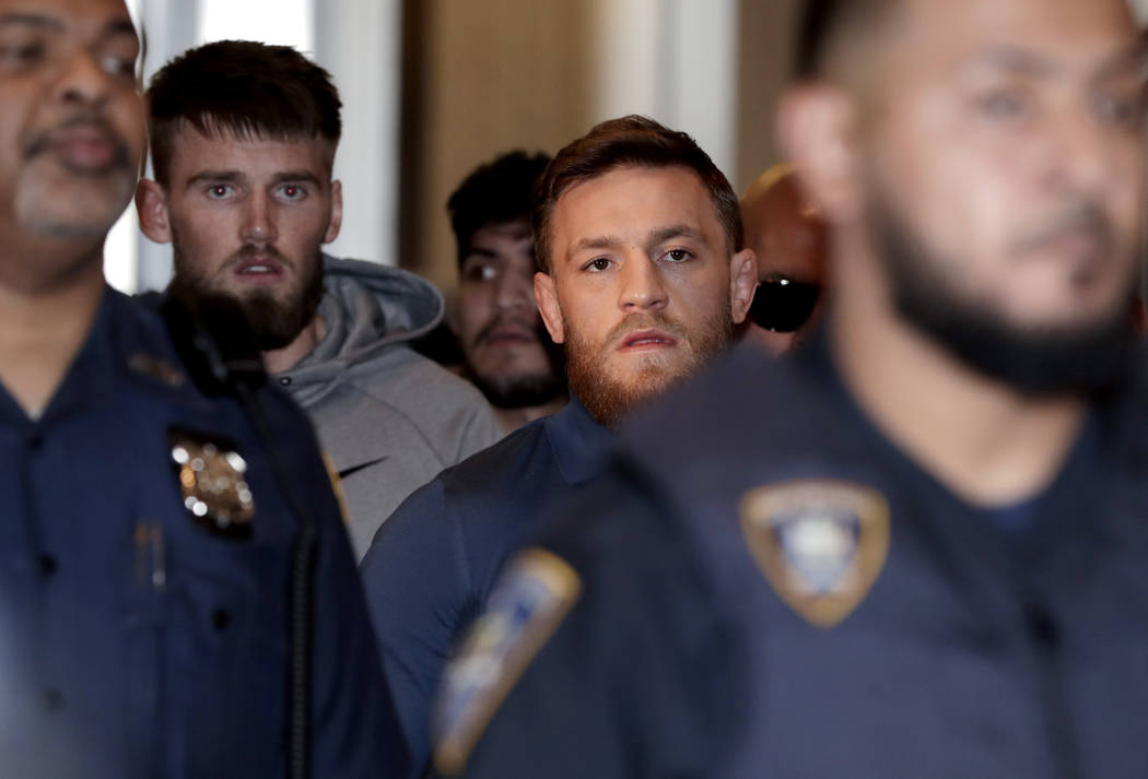 Ultimate fighting star Conor McGregor, center right, and his friend Cian Cowley, center left, also a mixed martial arts fighter, are escorted by New York Court Police officers after a hearing at t ...