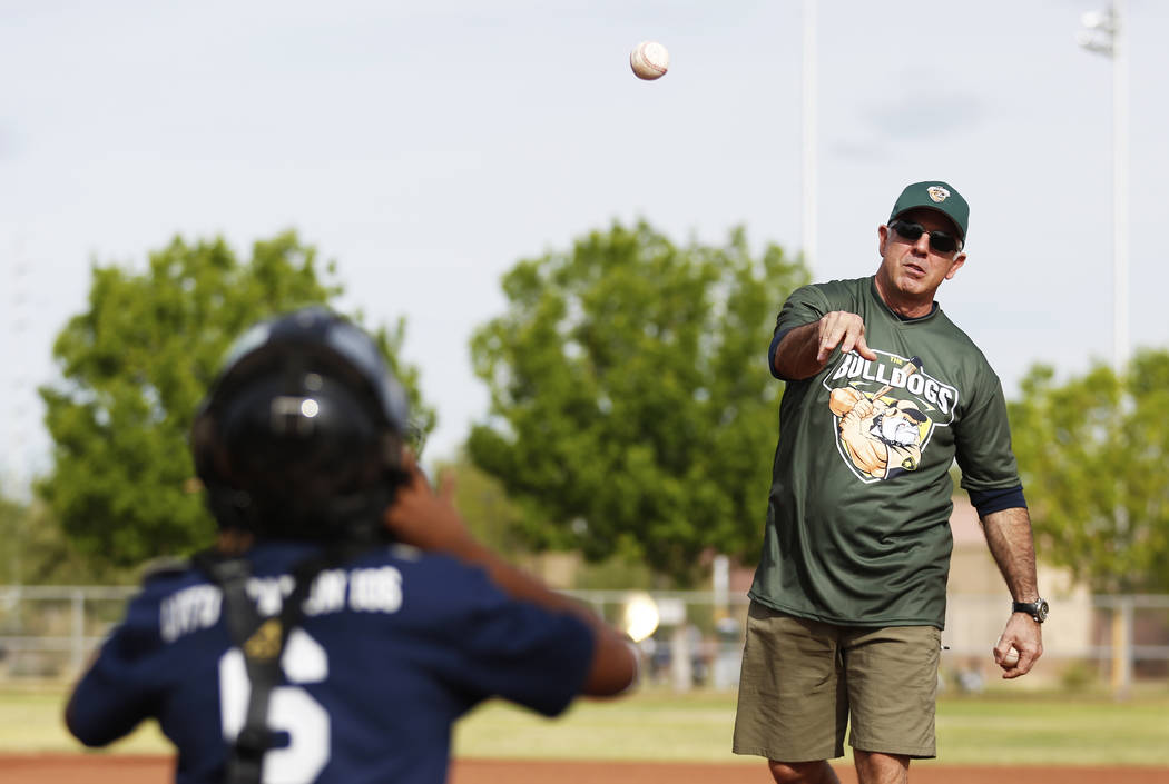 Clark County Sheriff Joe Lombardo practices his pitch with Shunta Hilliard, 11, during the Bolden Little League's Opening Day at Doolittle Field in Las Vegas on Saturday, April 7, 2018. Andrea Cor ...