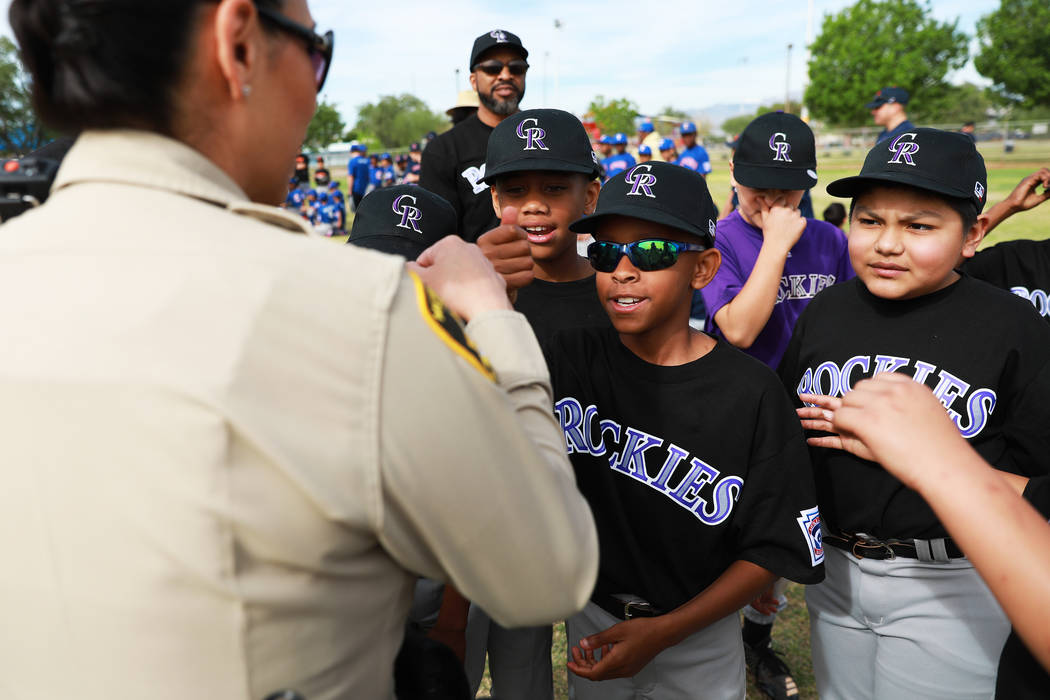From left, D'Terrion Bowman, 11, Justin Burrus, 10, and Esteban Cortez, 10, greet Yasenia Yatomi, bureau commander of Bolden Area Command, during the Bolden Little League's Opening Day at Doolittl ...