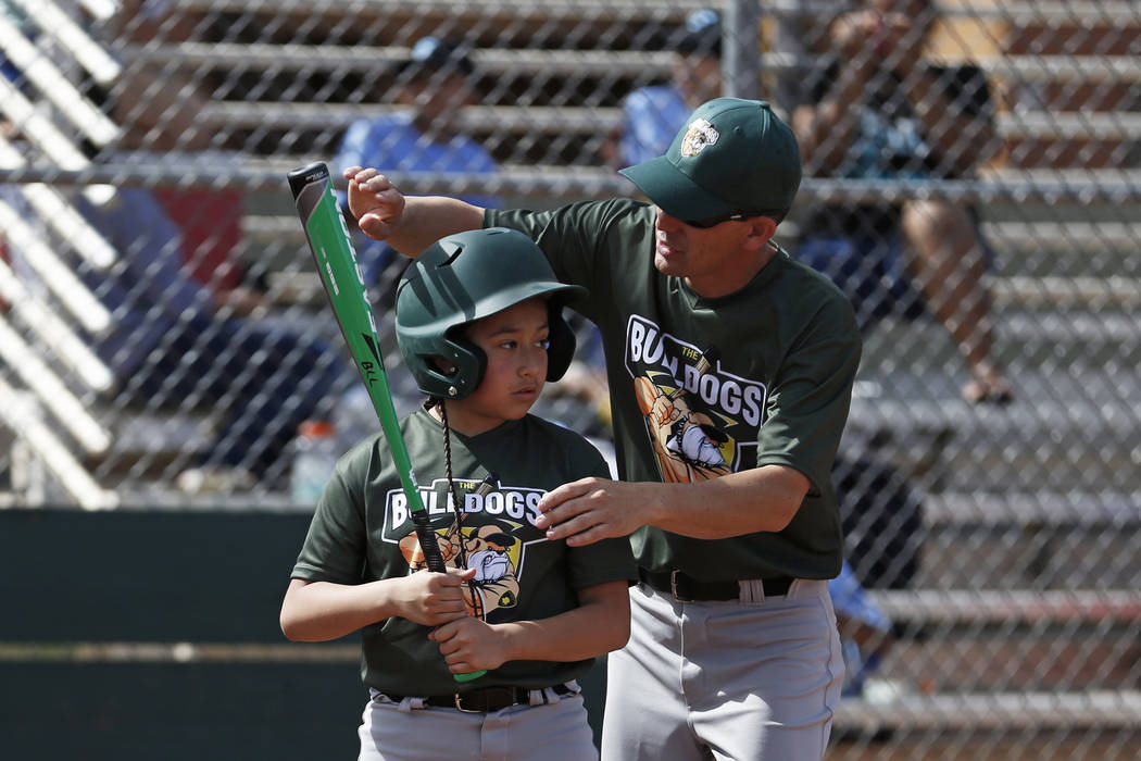 Marios West Side Bulldogs' head coach Dave Shive helps Natalie Zuniga with her swing during the Bolden Little League's Opening Day at Doolittle Field in Las Vegas on Saturday, April 7, 2018. Andre ...