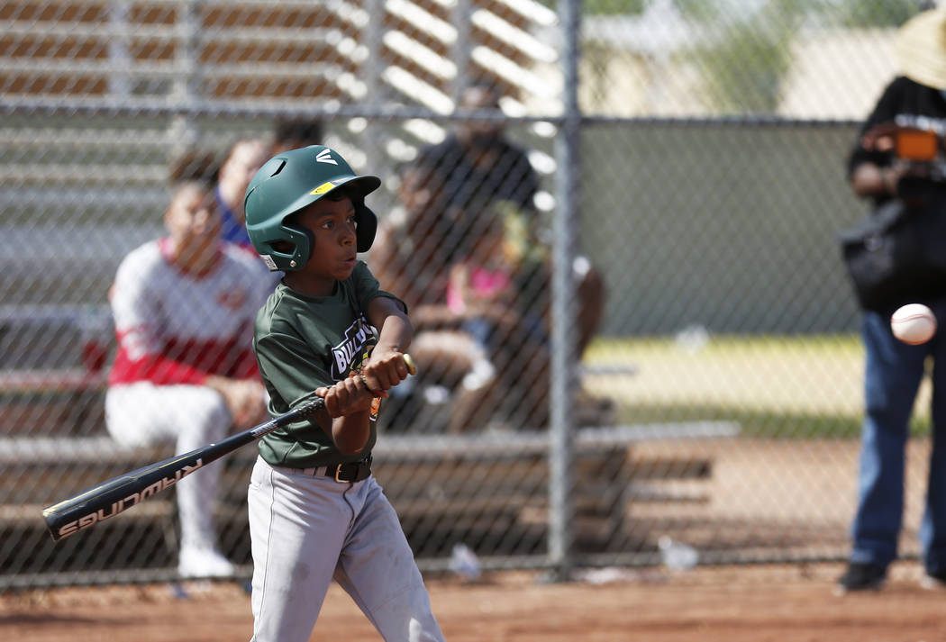 Marios West Side Bulldogs' pitcher Anthony Banisto swings against the Las Vegas Fire Department Engine 106 Red Sox during the Bolden Little League's Opening Day at Doolittle Field in Las Vegas on  ...