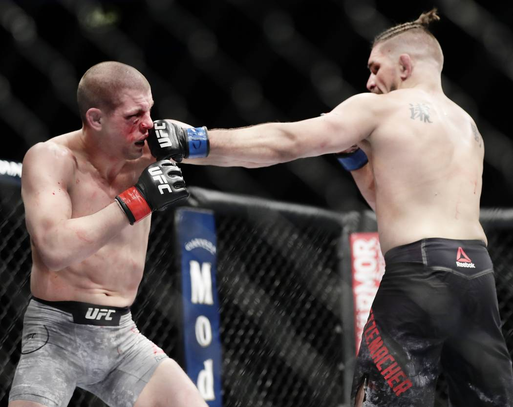 Chris Gruetzemacher, right, punches Joe Lauzon during the second round of a lightweight mixed martial arts bout at UFC 223, Saturday, April 7, 2018, in New York. Gruetzemacher stopped Lauzon after ...