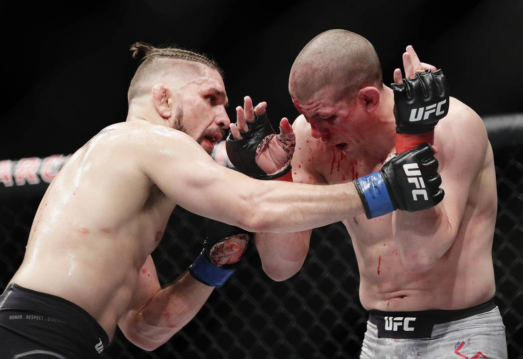 Chris Gruetzemacher, left, grapples with Joe Lauzon during the second round of a lightweight mixed martial arts bout at UFC 223, Saturday, April 7, 2018, in New York. Gruetzemacher stopped Lauzon  ...