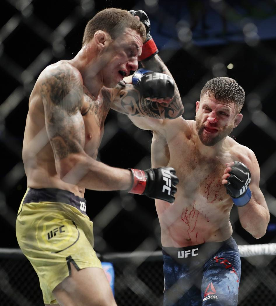 Brazil's Renato Moicano, left, deflects a punch by Calvin Kattar during the third round of a featherweight mixed martial arts bout at UFC 223 on Saturday, April 7, 2018, in New York. Moicano won t ...