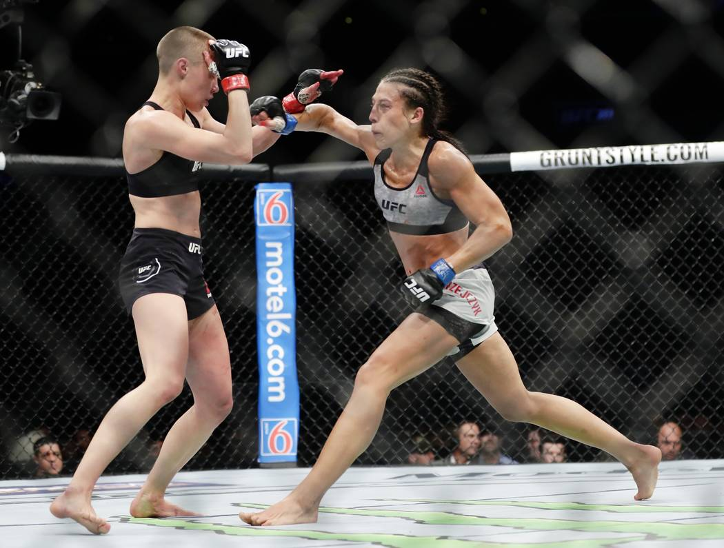 Rose Namajunas deflects a punch by Poland's Joanna Jedrzejczyk, right, during the fourth round of a women's strawweight title bout at UFC 223, early Sunday, April 8, 2018, in New York. Namajunas w ...