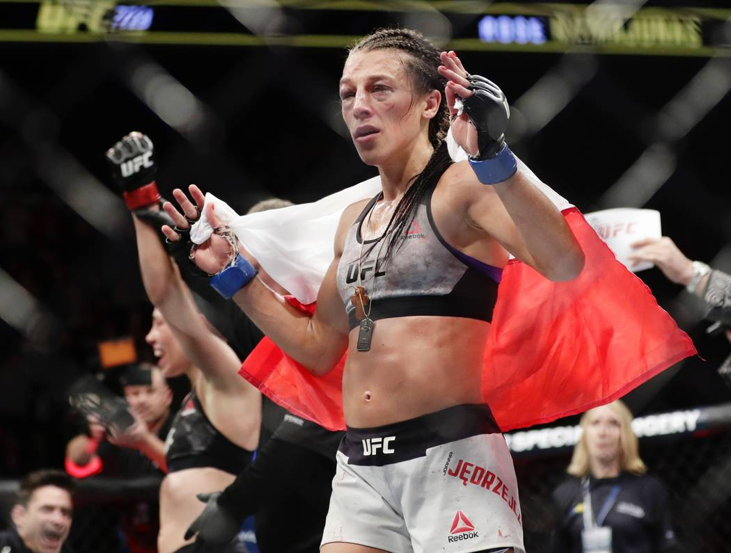 Poland's Joanna Jedrzejczyk, front, reacts after losing to Rose Namajunas in a women's strawweight title bout at UFC 223 early Sunday, April 8, 2018, in New York. Namajunas won the fight. (AP Phot ...