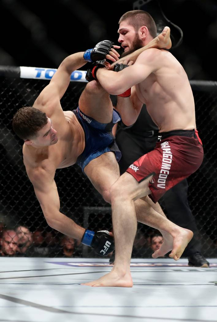 Russia's Khabib Nurmagomedov, right, throws Al Iaquinta during the first round of a lightweight title bout at UFC 223 early Sunday, April 8, 2018, in New York. Nurmagomedov won the fight. (AP Phot ...