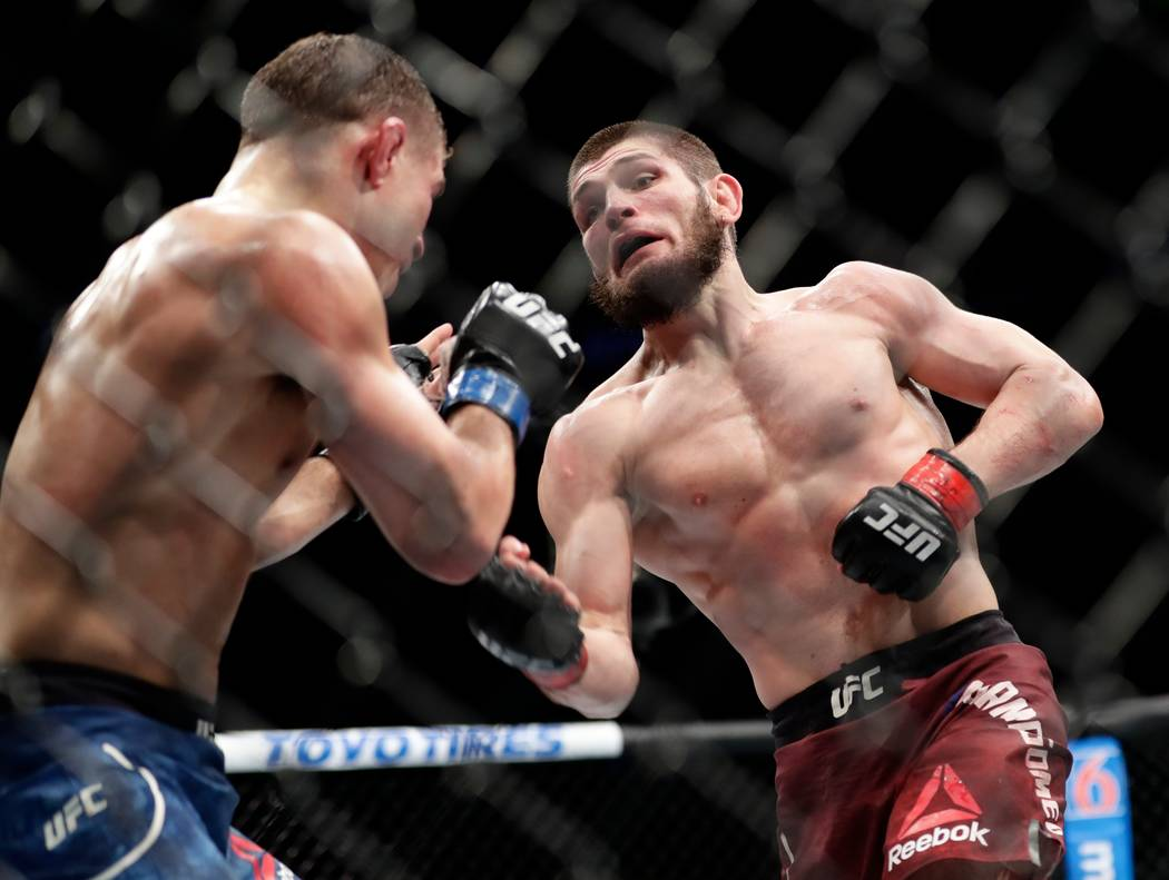 Al Iaquinta, left, deflects a punch from Russia's Khabib Nurmagomedov during the fifth round of a lightweight title bout at UFC 223 early Sunday, April 8, 2018, in New York. Nurmagomedov won the f ...