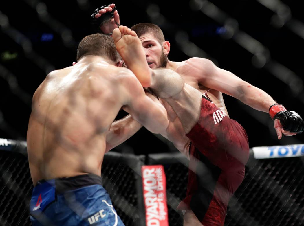 Russia's Khabib Nurmagomedov, right, kicks Al Iaquinta during the fifth round of a lightweight title bout at UFC 223 early Sunday, April 8, 2018, in New York. Nurmagomedov won the bout. (AP Photo/ ...