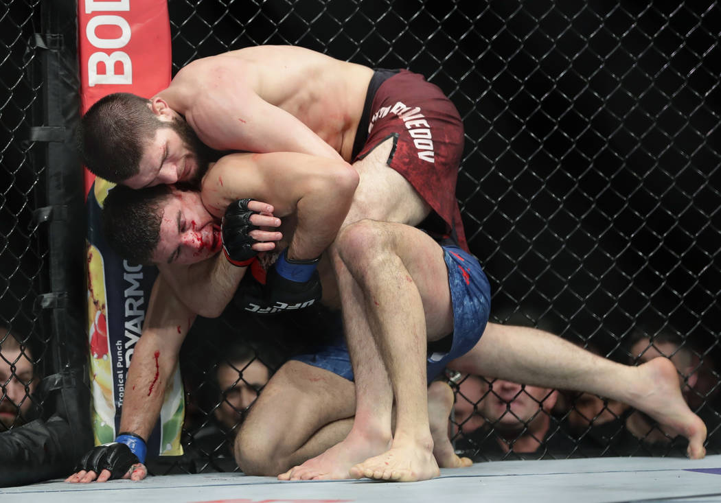 Russia's Khabib Nurmagomedov, above, wraps up Al Iaquinta during the fifth round of a lightweight title bout at UFC 223 early Sunday, April 8, 2018, in New York. Nurmagomedov won the fight. (AP Ph ...