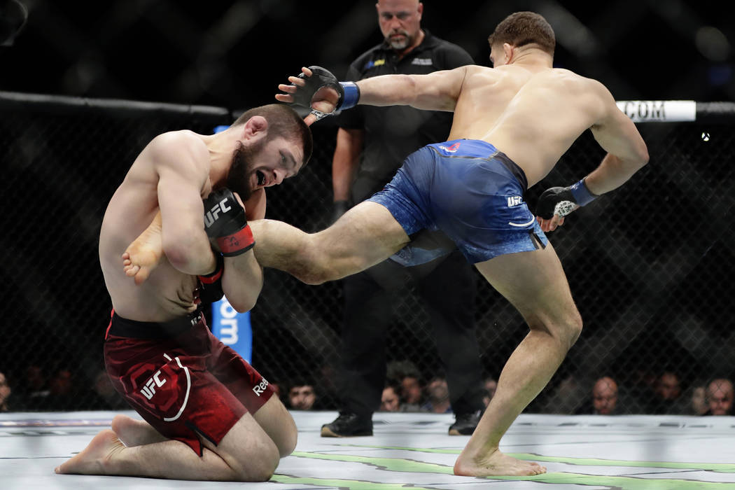 Russia's Khabib Nurmagomedov grabs the leg of Al Iaquinta during a lightweight title bout at UFC 223 early Sunday, April 8, 2018, in New York. Nurmagomedov won the bout. (AP Photo/Frank Franklin II)