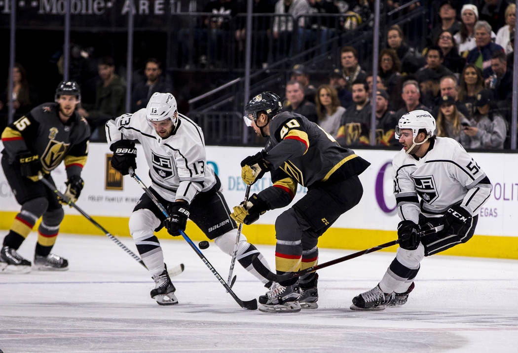 Los Angeles Kings left wing Kyle Clifford (13) and Vegas Golden Knights center Ryan Carpenter (40) fight over the puck during the first period of an NHL hockey game at T-Mobile Arena on Tuesday, F ...