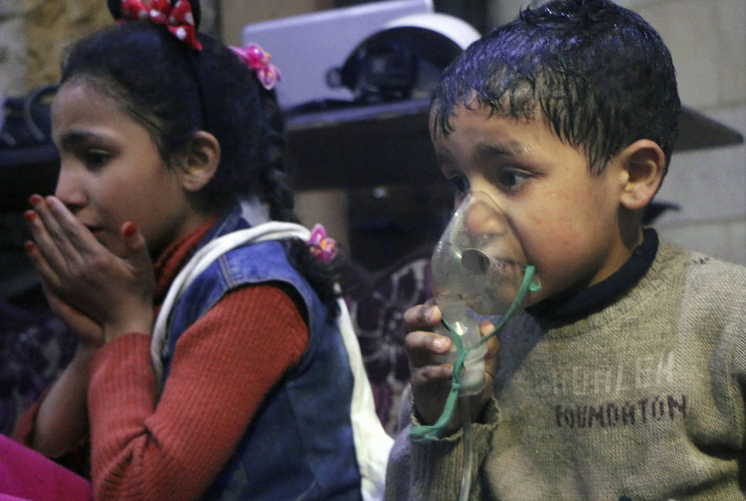 A child receives oxygen through respirators following an alleged poison gas attack in the rebel-held town of Douma, near Damascus, Syria, Sunday, April 8, 2018. Syrian rescuers and medics said the ...