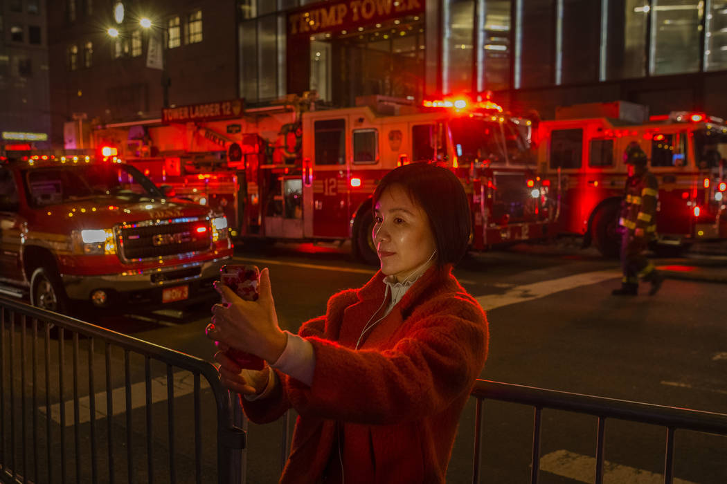A woman takes a selfie photo as firefighters work in front of Trump Tower in New York after a fire Saturday, April 7, 2018. The fire department says a blaze broke out on the 50th floor of the buil ...