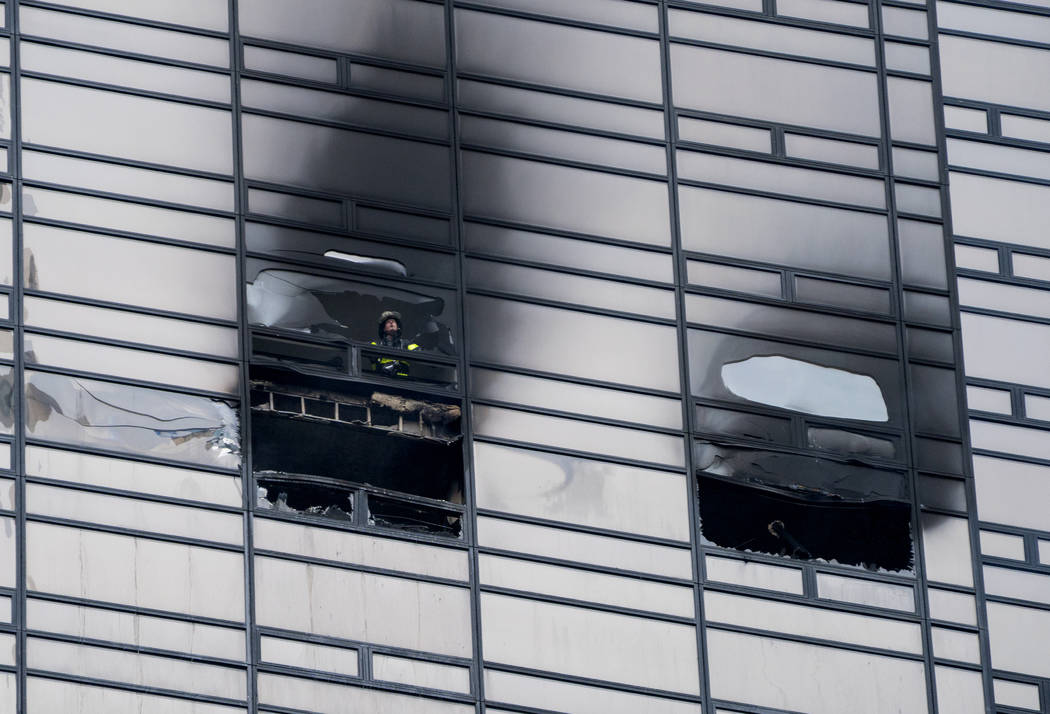 A firefighter looks out from the window of a fire damaged apartment in Trump Tower in New York on  Saturday, April 7, 2018. The fire department says the blaze broke out on the 50th floor shortly b ...