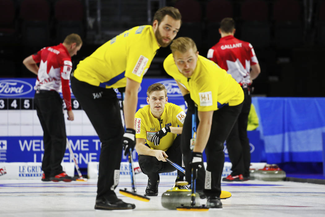 Team Sweden's Christoffer Sundgren delivers the rock to sweepers Oskar Eriksson, left, and Niklas Edin during the World Men's Curling Championship against Canada at the Orleans Arena in Las Vegas  ...