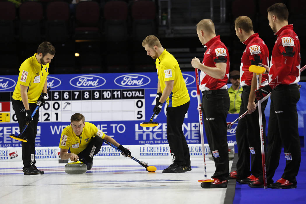 Team Sweden's Christoffer Sundgren delivers a stone to Oskar Eriksson, left, and Rasmus Wranaa against Canada during the World Men's Curling Championship at the Orleans Arena in Las Vegas on Sunda ...