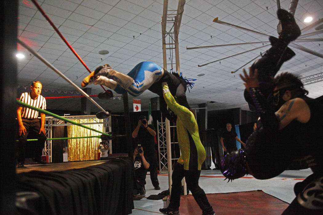 Atomico dives over Claustrophobia, center, as Madness dives on Local Crazy during a match at a Lucha Libre show at the Sahara Event Center in Las Vegas, Sunday, April 8, 2018. Rachel Aston Las Veg ...