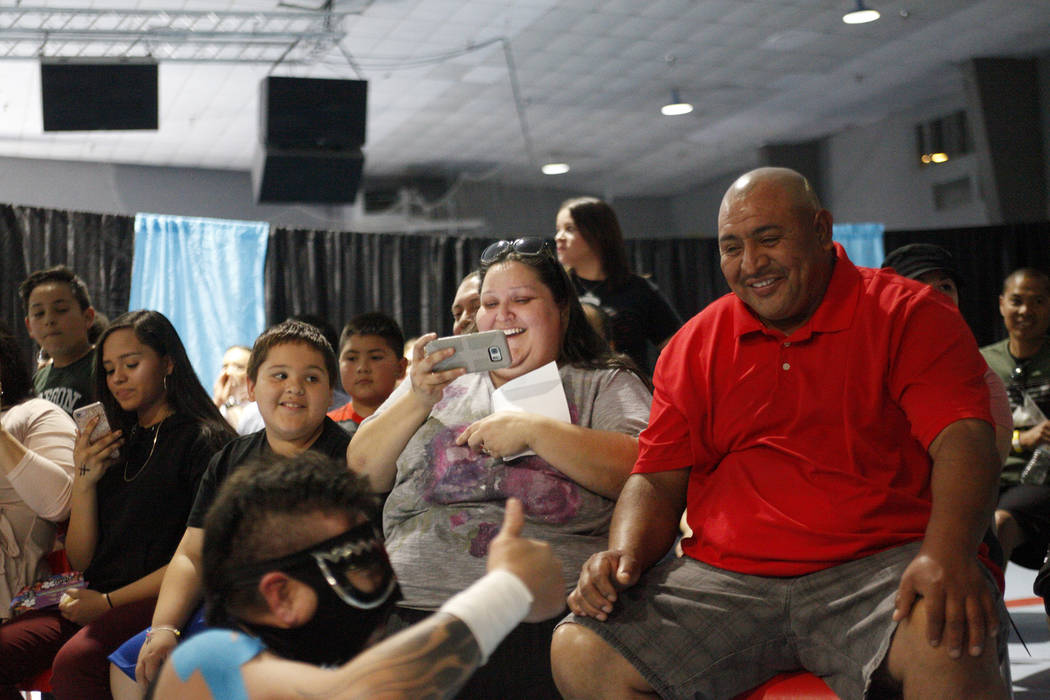 David Mendez, 7, from left, his mom Rachel Mendez, and his dad Alvaro Mendez laugh as Atomico lets the crowd know he's okay at a Lucha Libre show at the Sahara Event Center in Las Vegas, Sunday, A ...