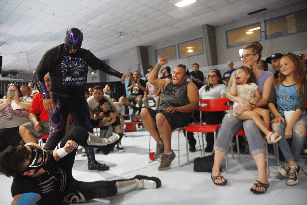 Madness laughs over Socal Crazy as Jorge Carreno, from left, his wife Brittany, his daughters Sofia, 3, and Kylie, 9, react during a match at a Lucha Libre show at the Sahara Event Center in Las V ...