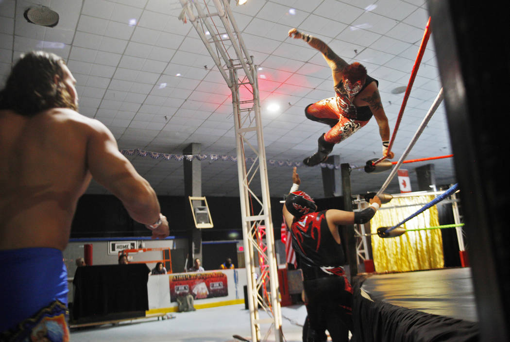 Black Danger dives over the ring onto his partner Black Boy as their opponent Ricky Mandel watches on during a match at a Lucha Libre show at the Sahara Event Center in Las Vegas, Sunday, April 8, ...