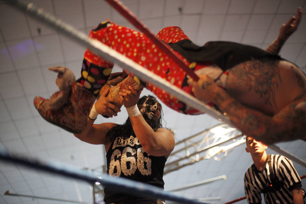 Bestia 666 holds Sinn Bodhi over the ropes during a match at a Lucha Libre show at the Sahara Event Center in Las Vegas, Sunday, April 8, 2018. Rachel Aston Las Vegas Review-Journal @rookie__rae