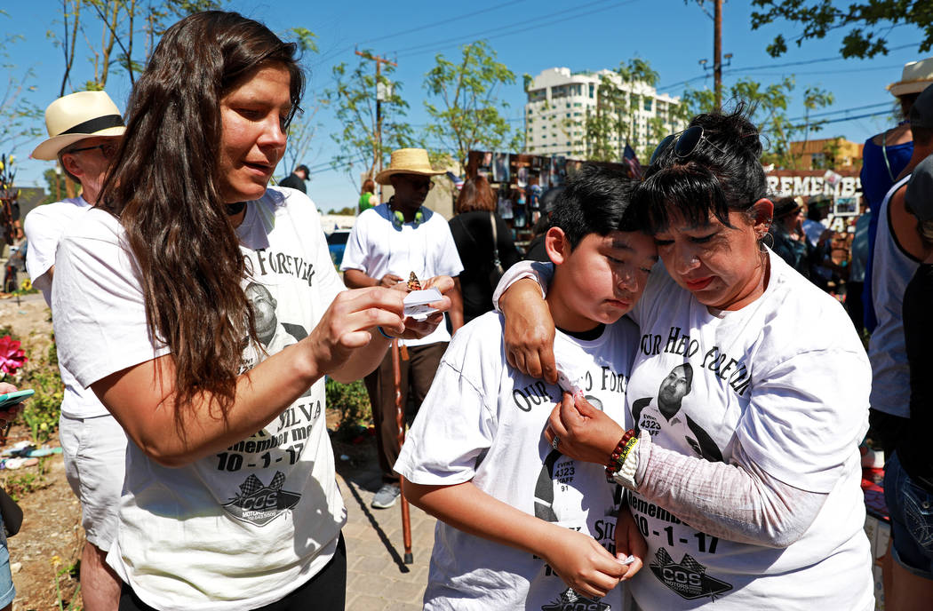 Amanda Cavero, left, releases a butterfly while Angelica Cervantes, right, embraces her son Arturo Delarosa, 11, during a commemorative butterfly release ceremony at the Healing Garden in Las Vega ...