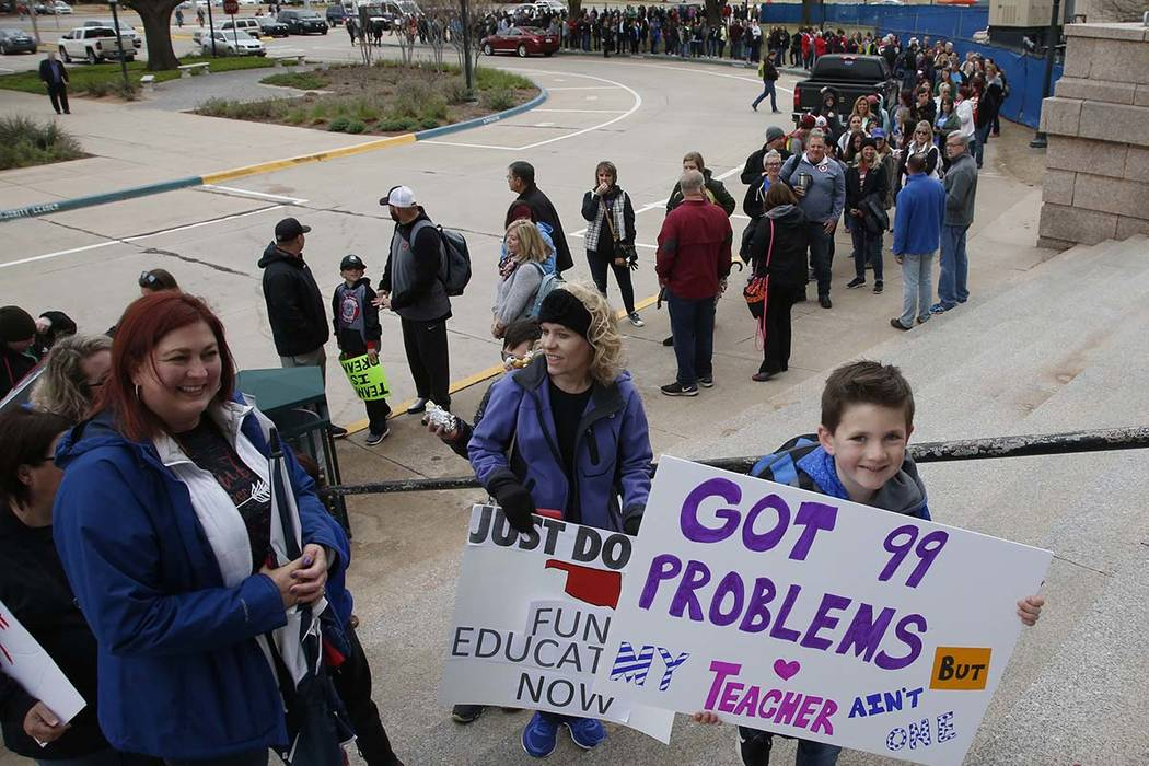 Six-year-old Coe Amos, a student in the Deer Creek school district of Edmond, Okla., stands in line to enter the state Capitol on the fifth day of protests over school funding, in Oklahoma City, F ...