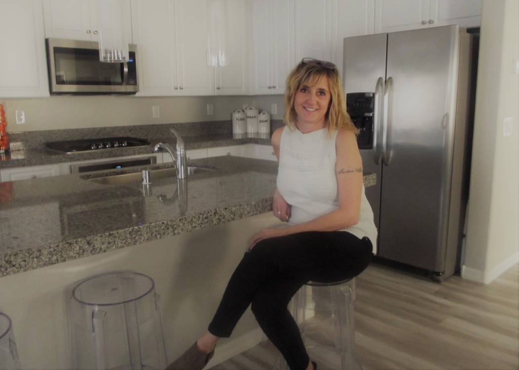 Michelle Walter enjoys the island kitchen overlooking the great room of her new two-story home that she purchased on contingency from CalAtlantic Homes through the Nevada Builder Trade In Program, ...