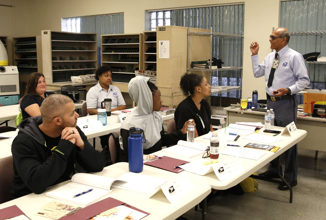 Orion Benezra, left, Khaleelah Valerie, front center, listen as the U.S. Postal Service City Carrier Instructor, Valentino Diaz Jr., teaches a class for mail carriers on preventing dog bites on Tu ...