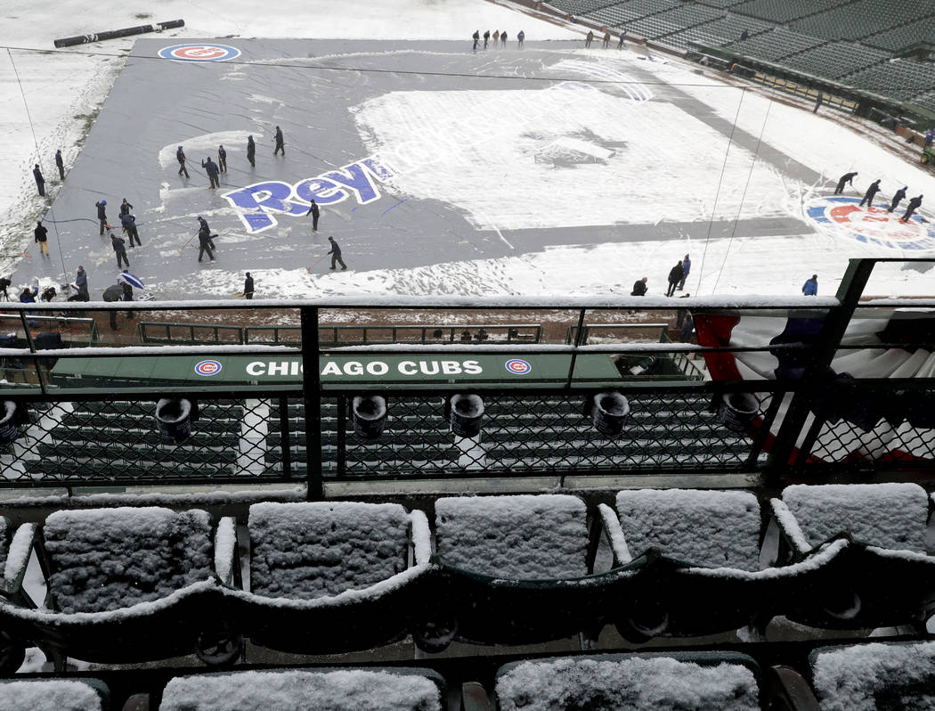 Members of the grounds crew clear snow at Wrigley Field in Chicago, Monday, April 9, 2018. The Chicago Cubs game against the Pittsburgh Pirates was postponed a day because of persistent snow that  ...